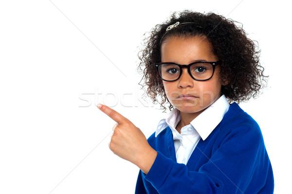 Studio shot of a melancholic girl pointing sideways Stock photo © stockyimages