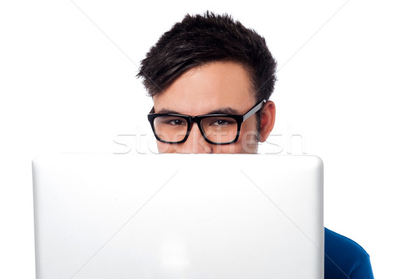 Mischievous boy hiding his face with laptop Stock photo © stockyimages