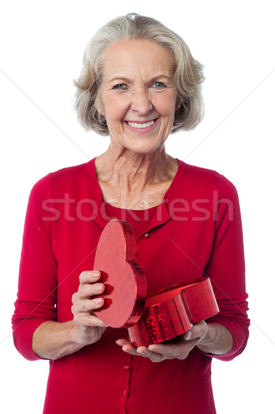 Stock photo: Senior woman with heart shaped gift box