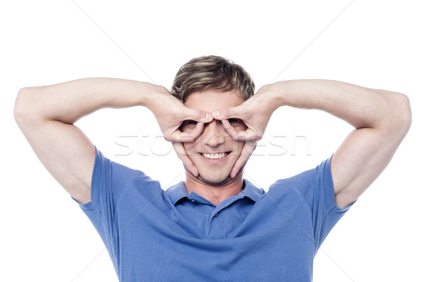 Handsome young man gesturing and smiling Stock photo © stockyimages