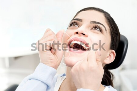 Dents femme nettoyage soie dentaire Photo stock © stockyimages