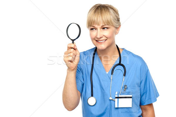 Stock photo: Pretty physician looking through magnifying glass