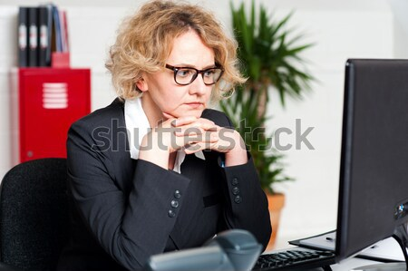 Thoughtful business lady seated in office Stock photo © stockyimages