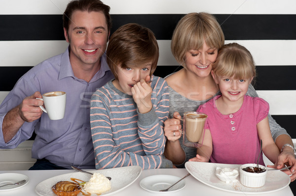 Family of four having great time in restaurant Stock photo © stockyimages