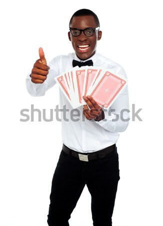 Young black man holding out deck of cards Stock photo © stockyimages