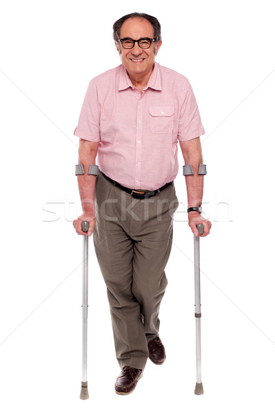 Smiling senior man walking with two crutches Stock photo © stockyimages
