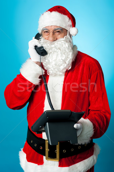 Modern Santa passing greetings over a phone call Stock photo © stockyimages