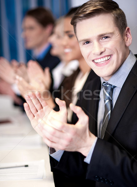 Stock photo: Business associates applauding, focus on guy