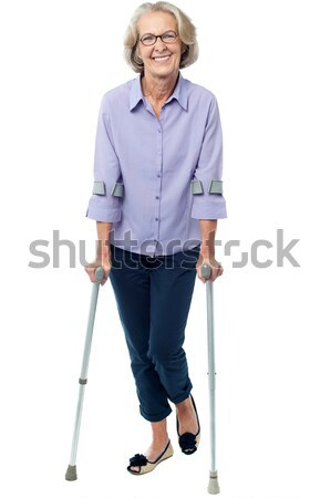 Old woman walking with crutches Stock photo © stockyimages
