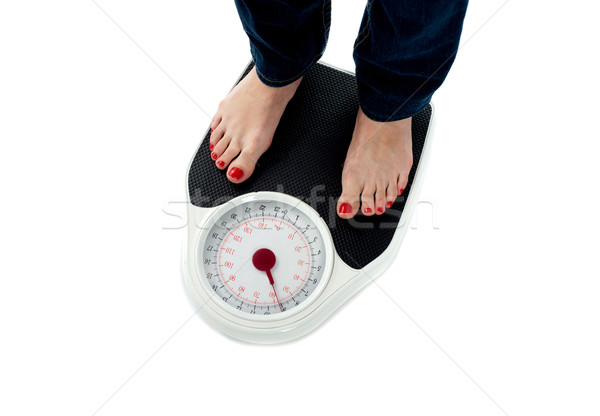 Woman standing on weighing scale, closeup of legs Stock photo © stockyimages