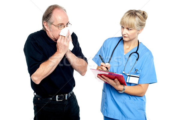 Aged male suffering from cold, sneezing Stock photo © stockyimages
