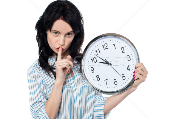 Stock photo: Young brunette with wall clock gesturing silence