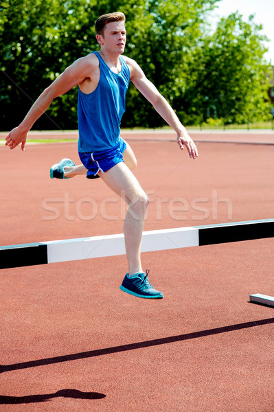 Male athlete jumping hurdle Stock photo © stockyimages