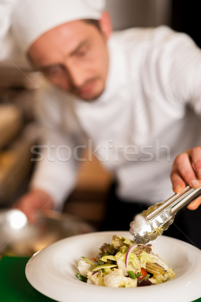 Chef arranging tossed salad in a white bowl Stock photo © stockyimages