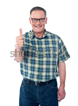 Casual old man showing thumbs-up sign to camera Stock photo © stockyimages