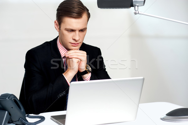 Serious businessman concentrating Stock photo © stockyimages