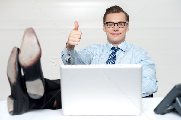 Thumbs up guy relaxing with legs on work desk Stock photo © stockyimages