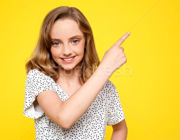 Smiling caucasian girl indicating upwards Stock photo © stockyimages