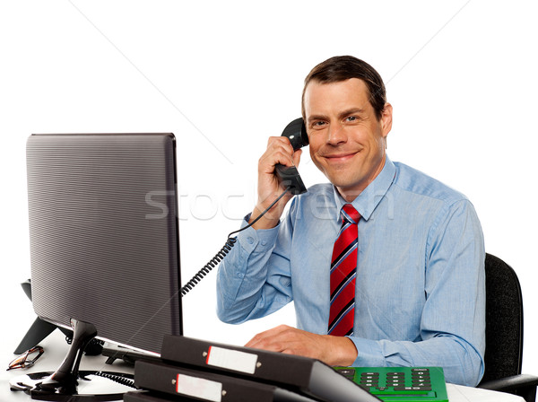 Businessman talking on phone, handling clients Stock photo © stockyimages