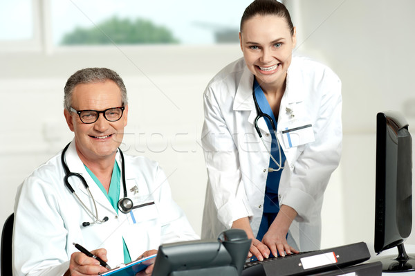Doctors team. Female assistant typing on keyboard Stock photo © stockyimages