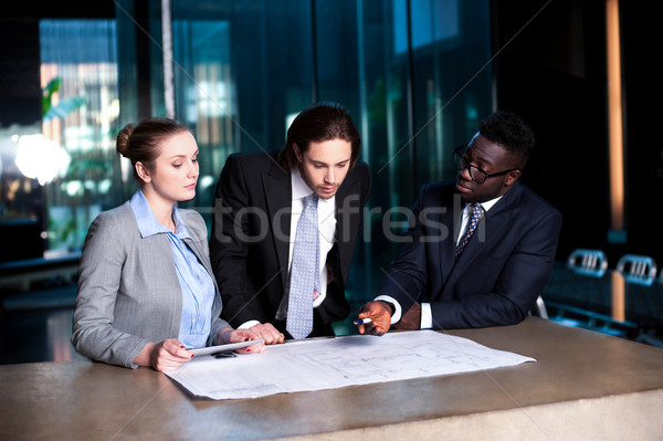 Business team of three reviewing project plan Stock photo © stockyimages