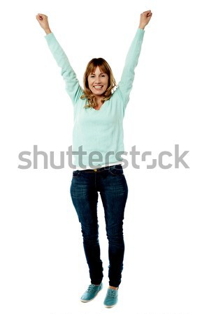 Female raising her arms in excitement Stock photo © stockyimages