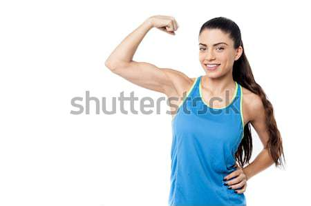 Sporty woman flexing her biceps Stock photo © stockyimages
