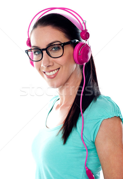 Pretty girl tuned into listening music via headphones Stock photo © stockyimages