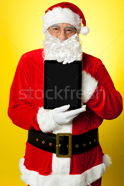 Kris Kringle presenting new updated tablet pc Stock photo © stockyimages