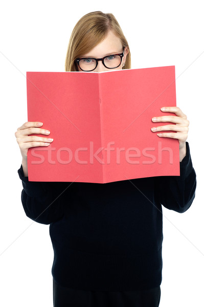 Student with a red book learning intently Stock photo © stockyimages