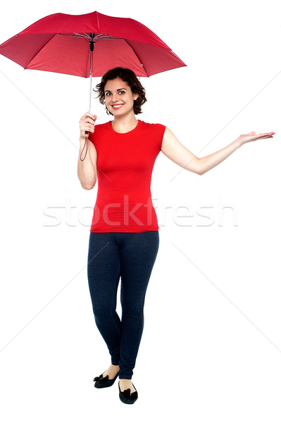 Woman with an umbrella reaches out to see if its raining Stock photo © stockyimages
