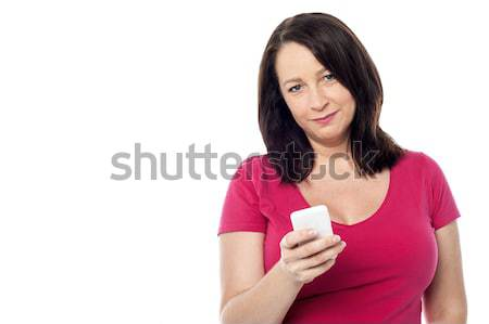 Beautiful woman using mobile phone Stock photo © stockyimages