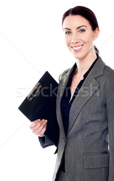 Smiling female secretary holding clipboard Stock photo © stockyimages
