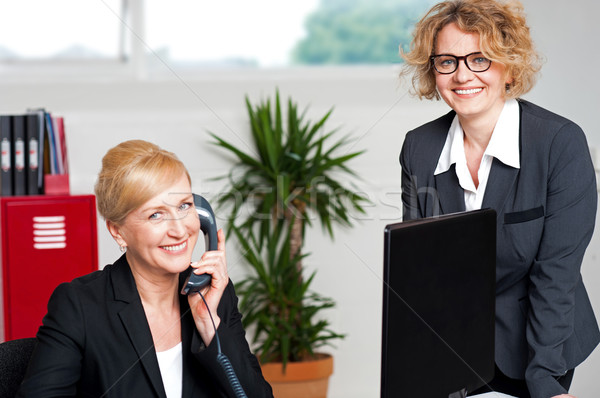 Woman attending call with colleague beside her Stock photo © stockyimages