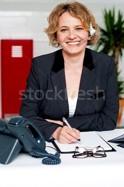Female executive assisting customers on call Stock photo © stockyimages