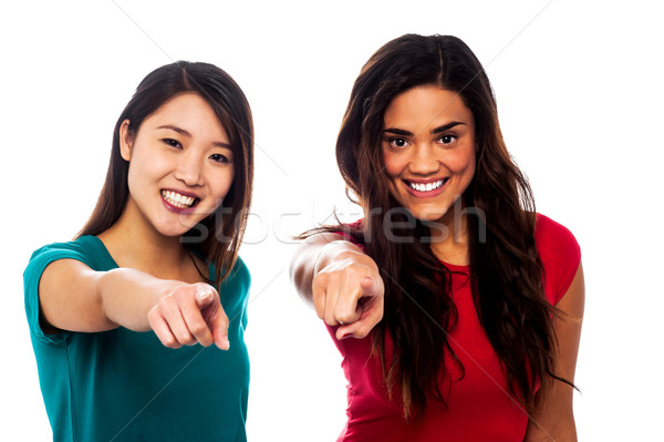 Pretty girls pointing finger towards you Stock photo © stockyimages