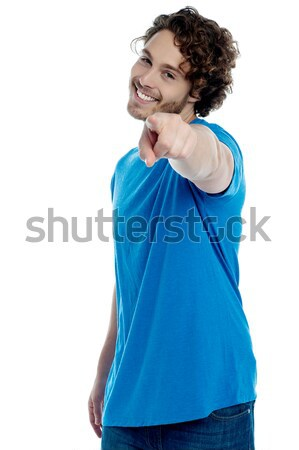 Handsome young man pointing towards camera Stock photo © stockyimages