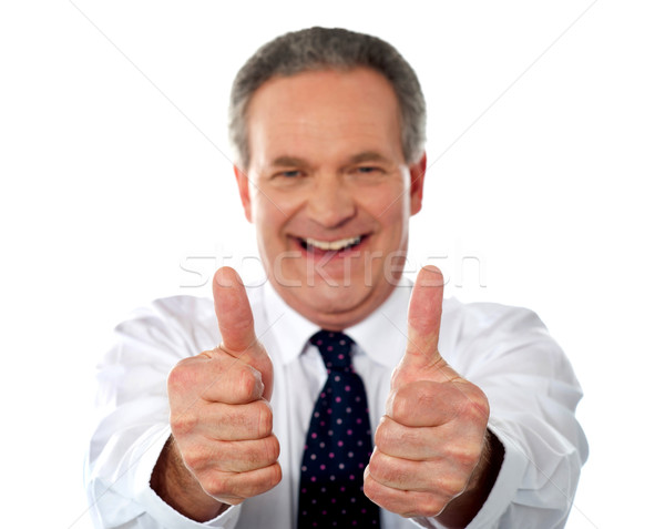 Happy businessman gesturing double thumbs-up Stock photo © stockyimages