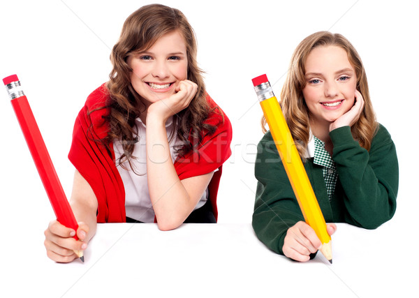 Beautiful schoolgirls posing with big pencil Stock photo © stockyimages