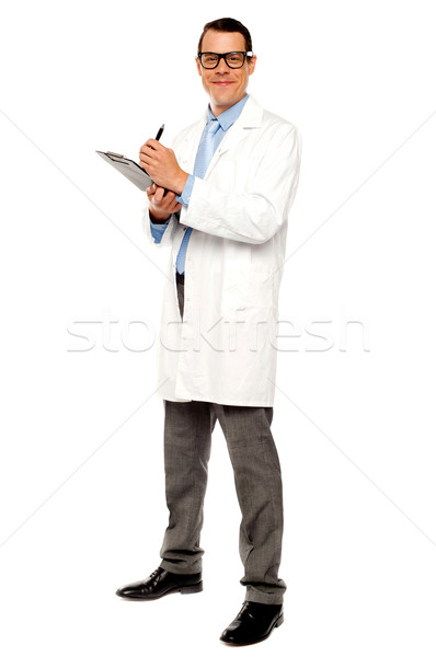 Young physician writing medical report Stock photo © stockyimages