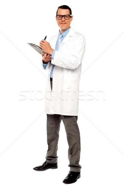 Młodych lekarz piśmie medycznych sprawozdanie odizolowany Zdjęcia stock © stockyimages