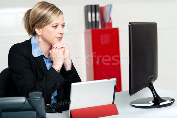 Corporate lady looking into computer screen Stock photo © stockyimages