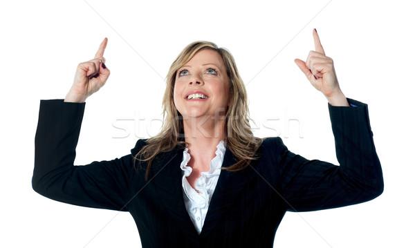 Female executive pointing upwards Stock photo © stockyimages