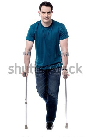 Painful expression by young man walking with help of crutches Stock photo © stockyimages