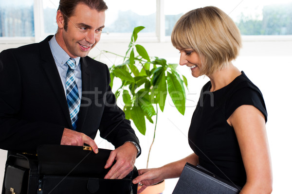 Boss opening his briefcase in front of secretary Stock photo © stockyimages