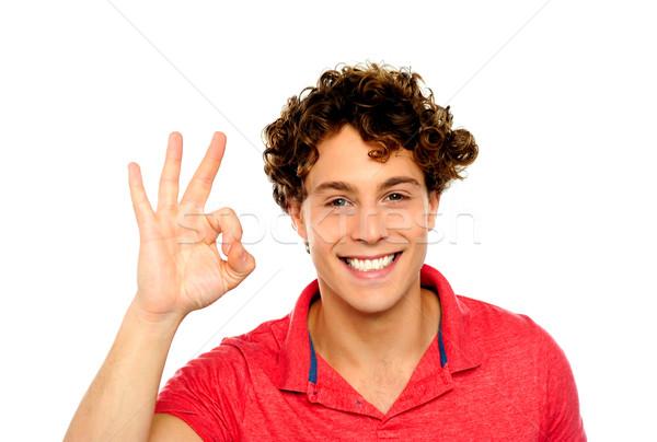 Kıvırcık saçlı adam mükemmellik imzalamak yalıtılmış Stok fotoğraf © stockyimages