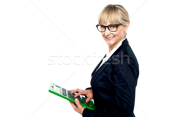 Bespectacled entrepreneur using a calculator Stock photo © stockyimages