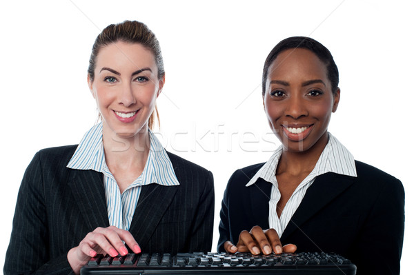 Female secretaries typing in keyboard Stock photo © stockyimages