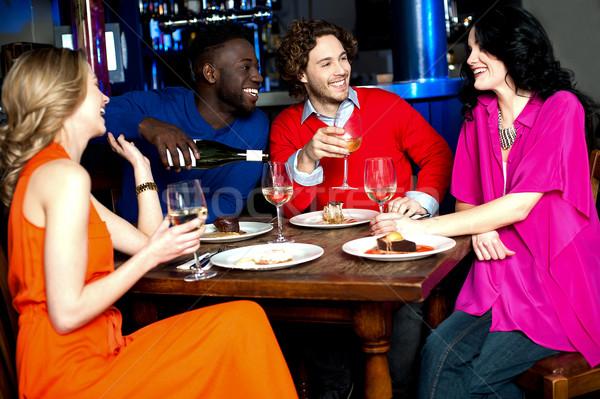 Tempo de festa quatro amigos bebidas restaurante Foto stock © stockyimages