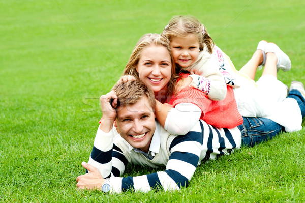 Smiling family of three piled on top of each other Stock photo © stockyimages